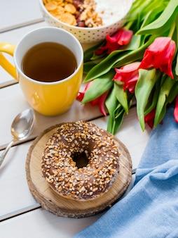 Heerlijke yoghurtkom met cornflakes, noten en jam op een witte houten lijst. gezond en biologisch voedingsconcept. tulpen met kopje thee, donut en ontbijt. bovenaanzicht
