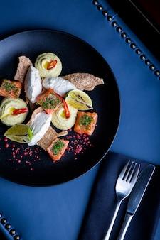 Heerlijke zalm met paté en hummus in restaurant. gezond exclusief voedsel op grote zwarte schotelclose-up