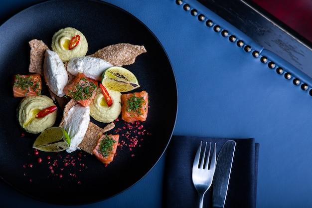 Heerlijke zalm met pate en hummus in restaurant. gezond exclusief voedsel op grote zwarte schotelclose-up