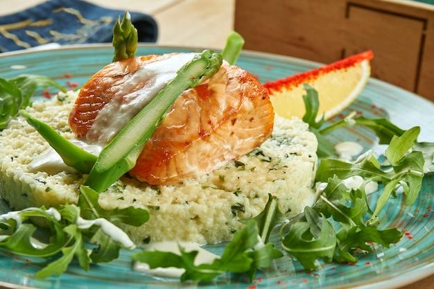 Heerlijke zalm steak met asperges, roomsaus en couscous garnituur op een blauw bord. lekker close-up en selectieve focus op voedsel.