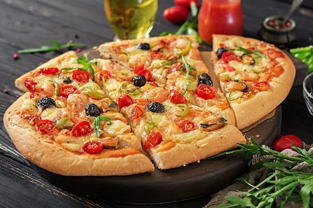Heerlijke zeevruchtengarnalen en mosselenpizza op een zwarte houten lijst.