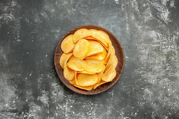 Heerlijke zelfgemaakte aardappelchips op een bruine plaat op grijs tafel stock beeld