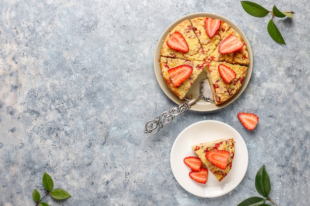 Heerlijke zelfgemaakte aardbei crumble cake met verse aardbeien plakjes, bovenaanzicht