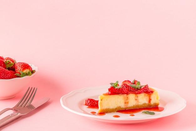 Heerlijke zelfgemaakte cheesecake met aardbeien op roze.