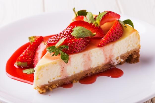 Heerlijke zelfgemaakte cheesecake met aardbeien op witte houten tafel.