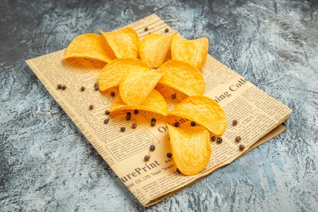 Heerlijke zelfgemaakte chips op krant op grijs tafel stock beeld