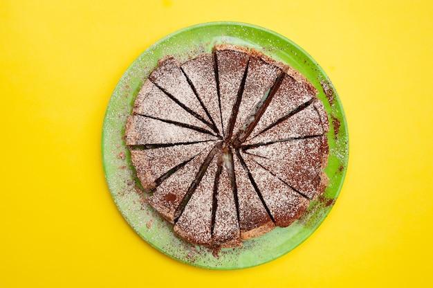 Heerlijke zelfgemaakte chocoladetaart met poedersuiker geïsoleerd op gele achtergrond