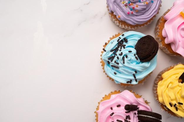 Heerlijke zelfgemaakte cupcakes met kleurrijke room en topping met snoep en chocoladekoekjes.