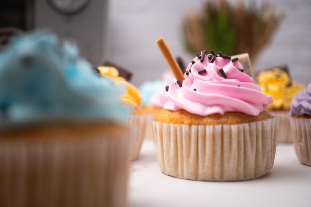 Heerlijke zelfgemaakte cupcakes met kleurrijke slagroom en topping met snoep en chocoladekoekjes. huisgemaakt herfstvakantiedessert