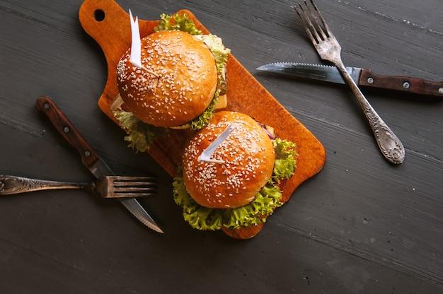 Heerlijke, zelfgemaakte hamburger om van te watertanden. op de houten tafel.