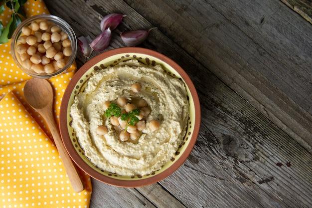 Heerlijke zelfgemaakte hummus pasta met olijfolie en kikkererwten. houten tafel. gezond eten.