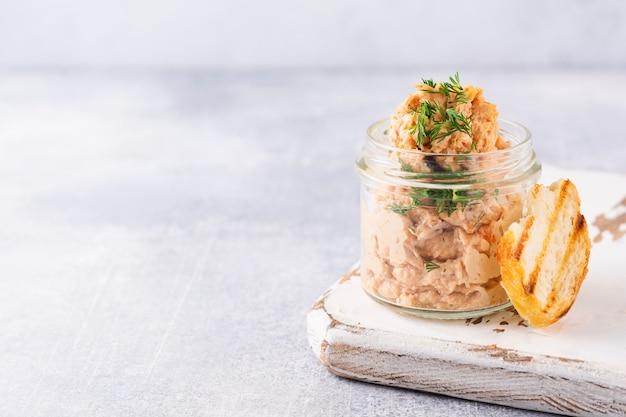 Heerlijke zelfgemaakte kippenpastei met kruiden en dille in een glazen pot en een sneetje brood in de buurt en kappertjes op een lichte bordtafel. selectieve aandacht.