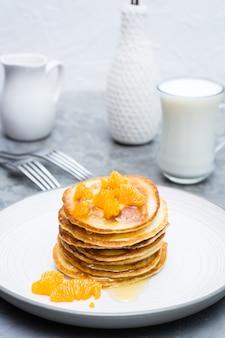 Heerlijke zelfgemaakte pannenkoeken met mandarijnen en honing, glas melk op een bord op de tafel