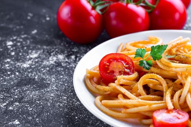Heerlijke, zelfgemaakte pasta met tomatensaus, peterselie, kruiden en groenten op een bord. italiaans eten