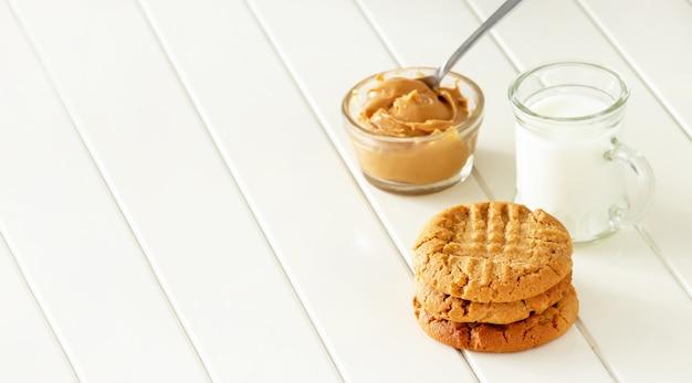 Heerlijke zelfgemaakte pindakaas koekjes met mok melk. witte houten ruimte. gezonde snack of lekker ontbijt concept. bannerformaat.
