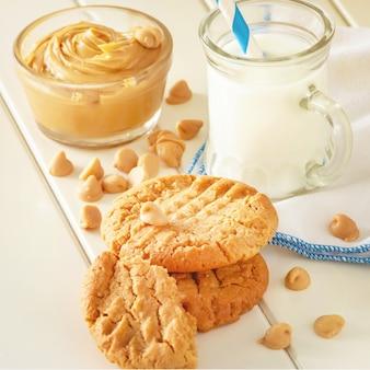 Heerlijke zelfgemaakte pindakaas koekjes met mok melk. witte houten ruimte. gezonde snack of lekker ontbijt concept. vierkant plaatje. getinte foto.