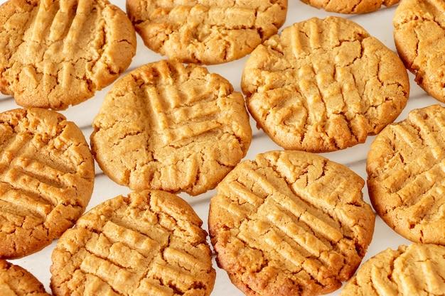 Heerlijke zelfgemaakte pindakaas koekjes op koeling rek. witte houten ruimte. gezond snackconcept.