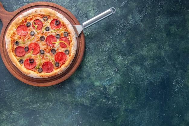 Heerlijke zelfgemaakte pizza op een houten snijplank aan de rechterkant op een donkere ondergrond