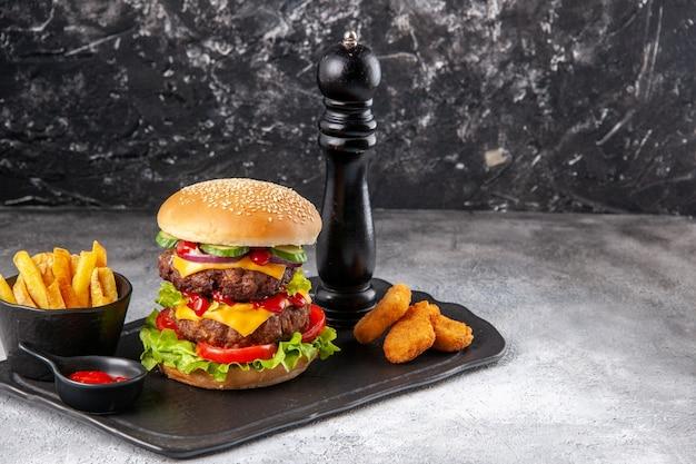 Heerlijke zelfgemaakte sandwich en ketchup frietjes kipnuggets op zwart bord aan de rechterkant op grijs verontrust oppervlak