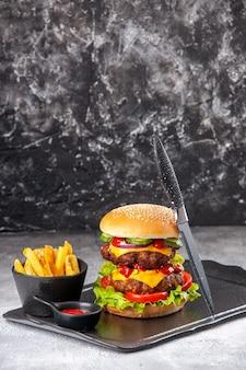 Heerlijke zelfgemaakte sandwich en vork ketchup frietjes groen op zwart bord op grijs geïsoleerd oppervlak