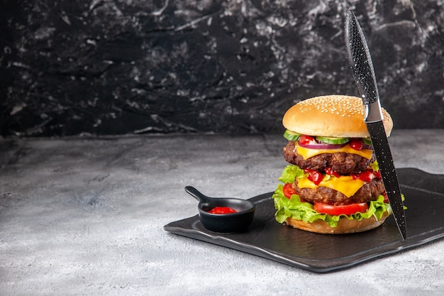 Heerlijke zelfgemaakte sandwich en vork op zwart dienblad aan de linkerkant op grijs verontrust geïsoleerd oppervlak