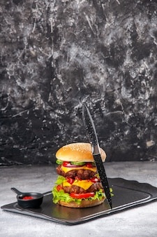 Heerlijke zelfgemaakte sandwich en vorkketchup op zwart dienblad op grijs verontrust geïsoleerd oppervlak