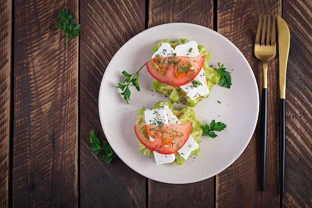 Heerlijke zelfgemaakte spinazie vegetarische wafels met fetakaas en tomaten. bovenaanzicht, plat gelegd
