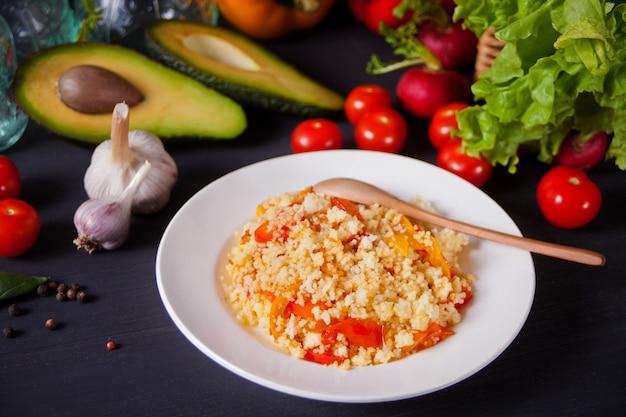Heerlijke zelfgemaakte vegetarische couscous met tomaten, wortelen, peper en verse basilicum op een donkere keukentafel met groenten op de achtergrond