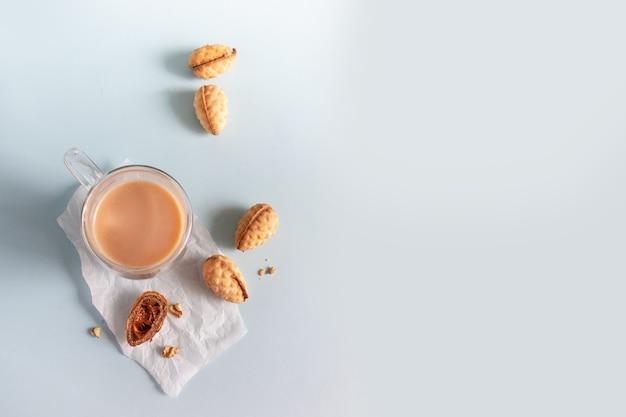 Heerlijke zelfgemaakte walnotenkoekjes in een kom en warme koffie op blauwe achtergrond met kopieerruimte.