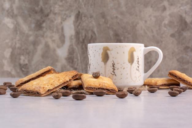 Heerlijke zoete crackers met witte kop koffie op zak. hoge kwaliteit foto