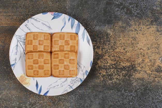 Heerlijke zoete crackers op kleurrijke plaat.