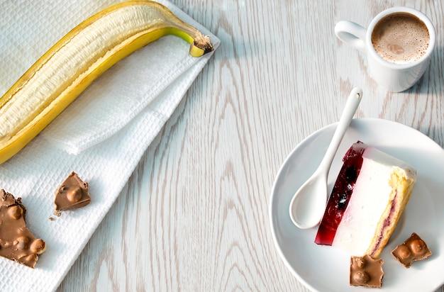 Heerlijke zoete dessert cheesecake, banaan, stukjes chokolates en kopje koffie op houten achtergrond. plat leggen, ruimte kopiëren.