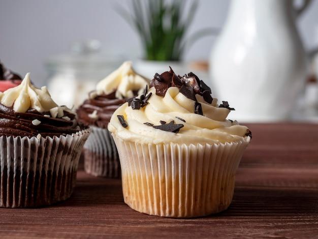 Heerlijke zoete handgemaakte chocolade cupcakes op een houten tafel. fijne zoetwaren. vooraanzicht