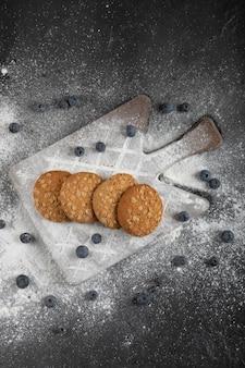 Heerlijke zoete koekjes op houten plank met bosbessen