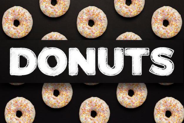 Heerlijke, zoete, verse donuts op een zwarte achtergrond. tekst donuts toegevoegd. patroon. concept van het ontbijt, fast food, coffeeshop, bakkerij, lunch. plat lag, bovenaanzicht.