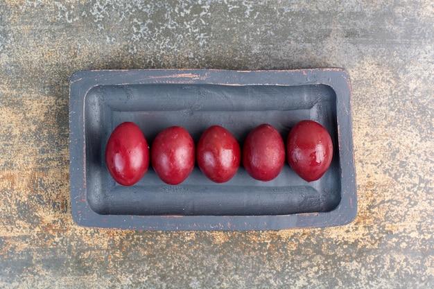 Heerlijke zoete vruchten in donker bord op marmeren achtergrond. hoge kwaliteit foto