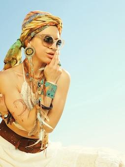 Heet afrikaanse stijl mode portret van een mooie jonge zittende vrouw met hoofdband