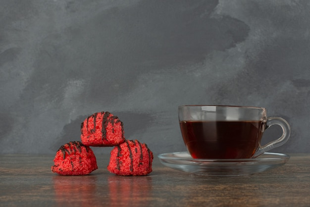 Heet, aroma thee met drie zoete snoepjes op marmeren achtergrond.