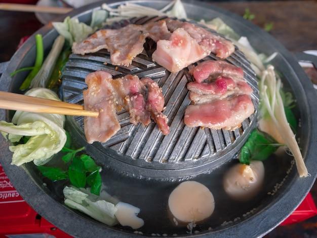 Heet buikvarkensvlees gesneden van thaise barbecuegrill of moo krata-pan op eetstokjes heet buikvarkensvlees gesneden van thaise barbecuegrill of moo krata-pan op eetstokjes