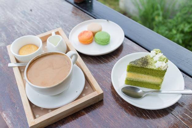 Heet koffieontbijt met groene theecake en verse makaron in gezellig terras
