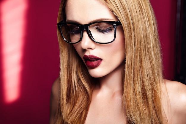 Heet mooi blond vrouwenmodel met verse dagelijkse make-up met donkere lippenkleur en schone gezonde huid op rode achtergrond in glazen