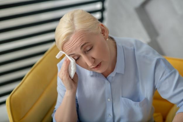 Heet, onwel. vrouwenblonde met gesloten ogen die haar gezicht afvegen met een servet dat ongelukkig voorhoofd fronst.
