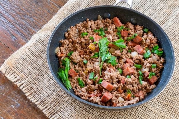 Heet sappig rundergehakt gekookt met kruiden, spek en peterselie in de koekenpan. gekookt rundergehakt