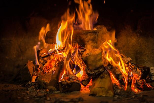 Heet vuur in duisternis op open haard op winter cottage