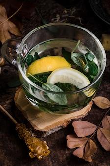 Heet water van hoge hoek met citroen en bladeren