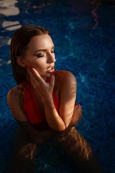 Heet wijfje in stijlvol zwempak. openluchtmanierportret van glamourdame die van haar vakantie op luxevilla in heet tropisch eiland geniet.