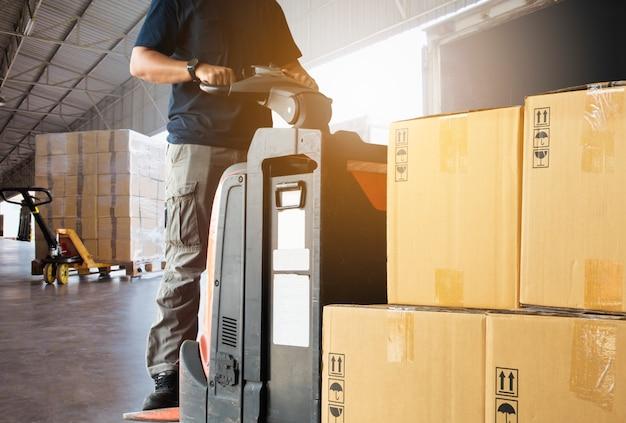 Heftruckchauffeur die de goederen van de palletverzending in een vrachtwagen laden