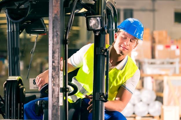 Heftruckchauffeur in beschermend vest rijden heftruck in magazijn van expeditiebedrijf