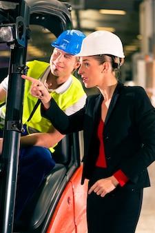 Heftruckchauffeur in magazijn van expeditiebedrijf, vrouwelijke supervisor of collega, wijzend