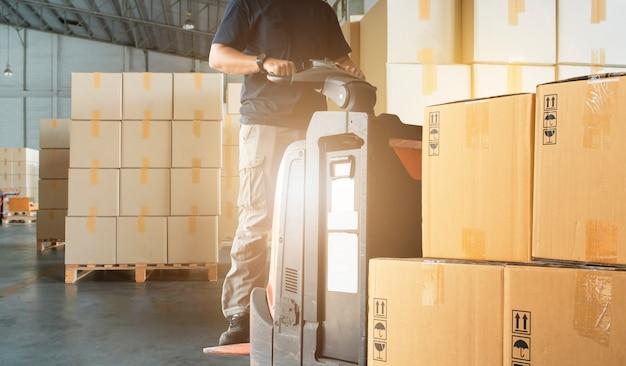 Heftruckchauffeur lossen dozen bij de opslag van het magazijn